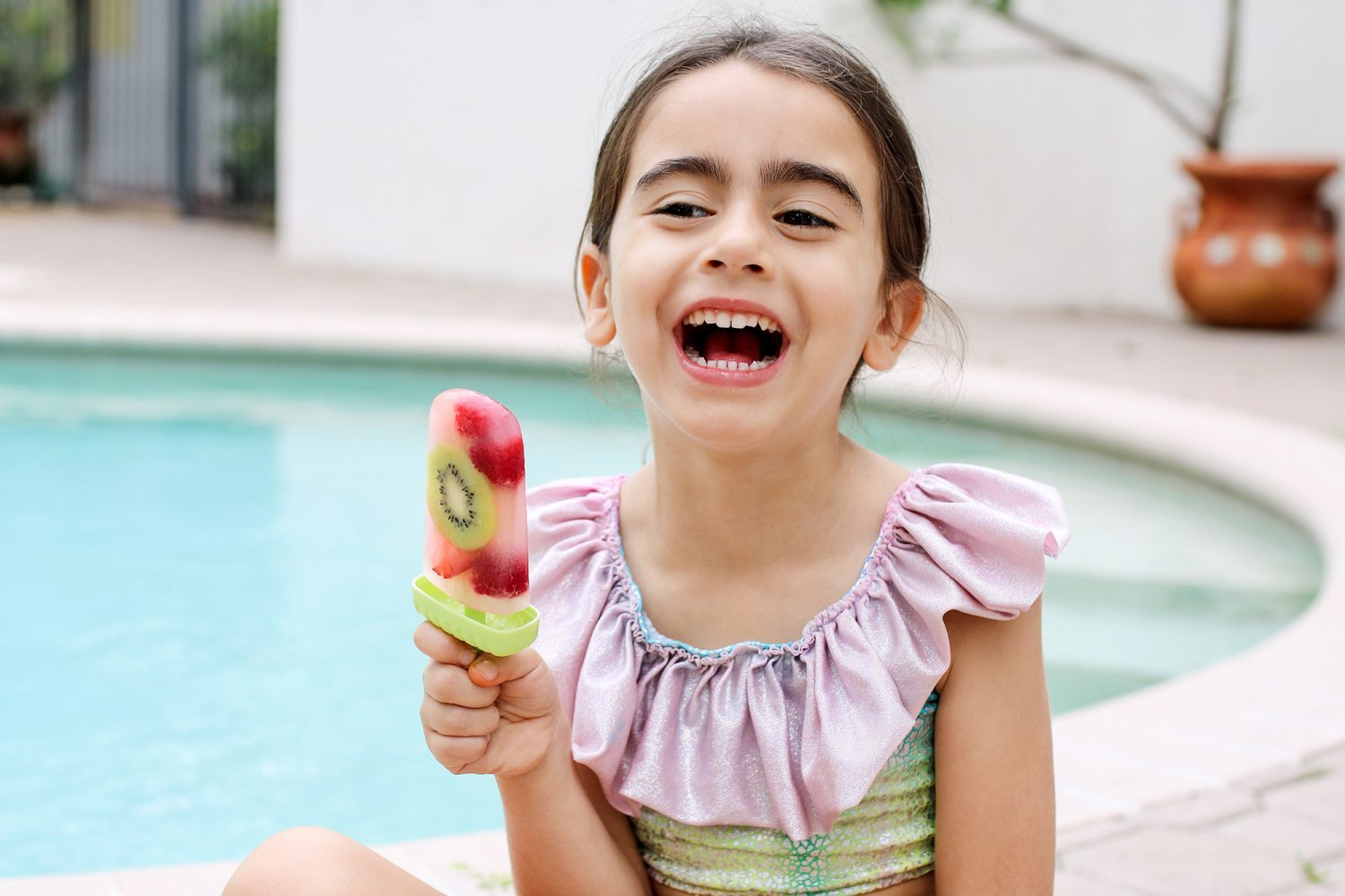 girl laughing while holding a fresh fruit popsicle