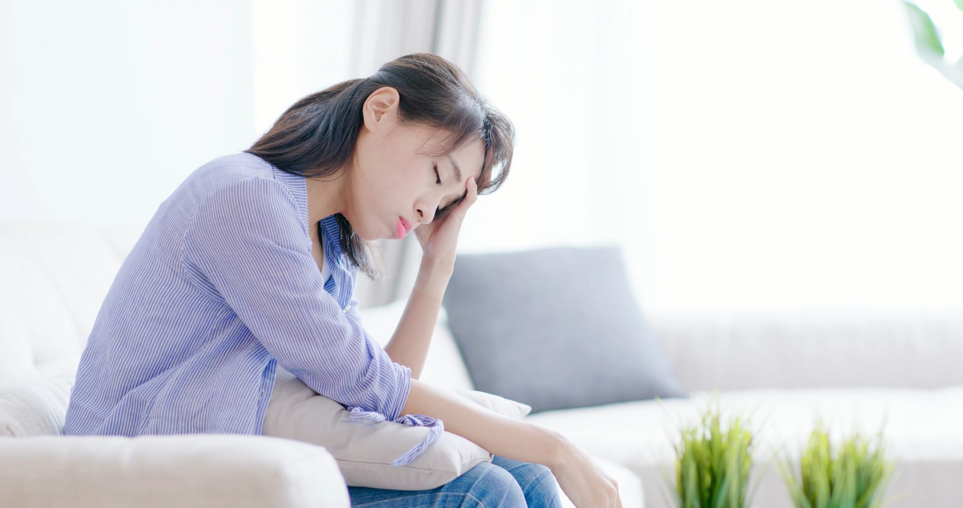 exhausted woman sitting on a couch possibly depressed or suffering from anxiety