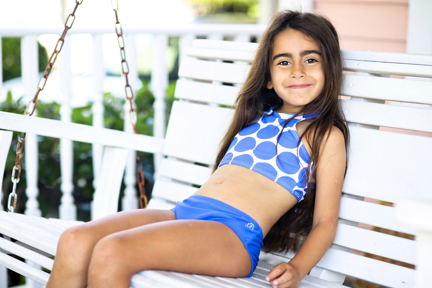 Beautiful girl wearing a swimsuit from SwimZip on a porch swing