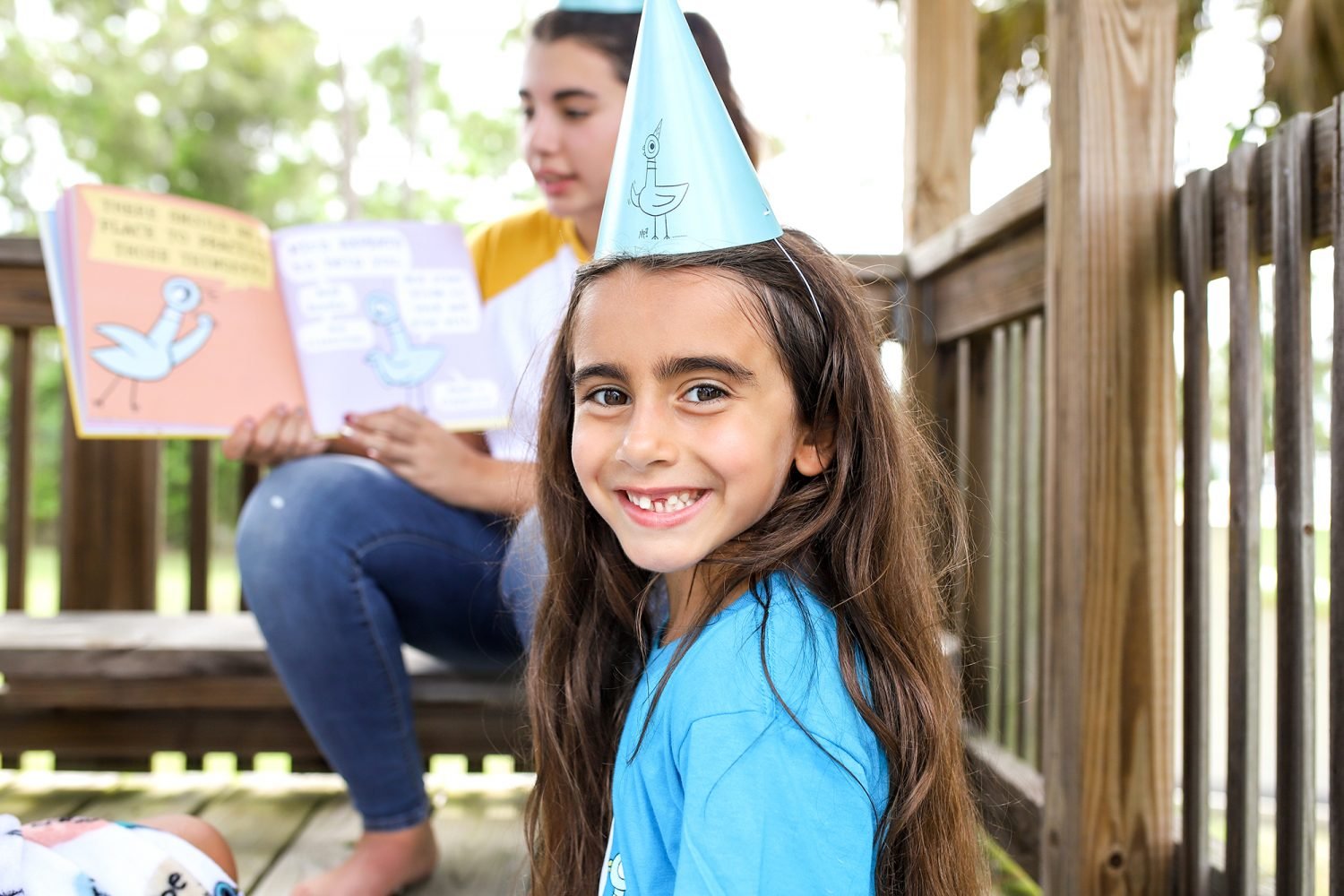 girl smiling with her mo willems pigeon bird-day hat during story time