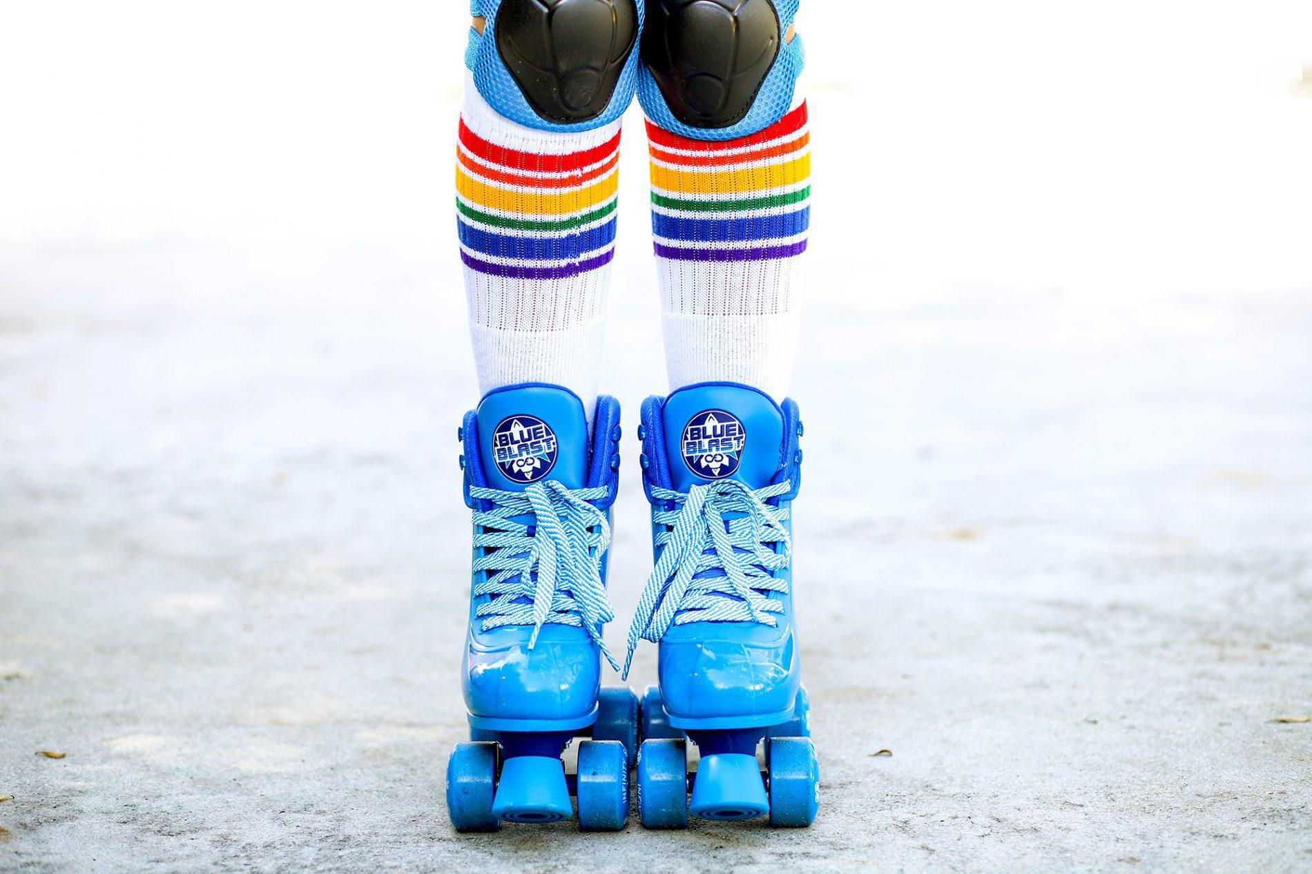 Kids blue roller skates with rainbow pride socks
