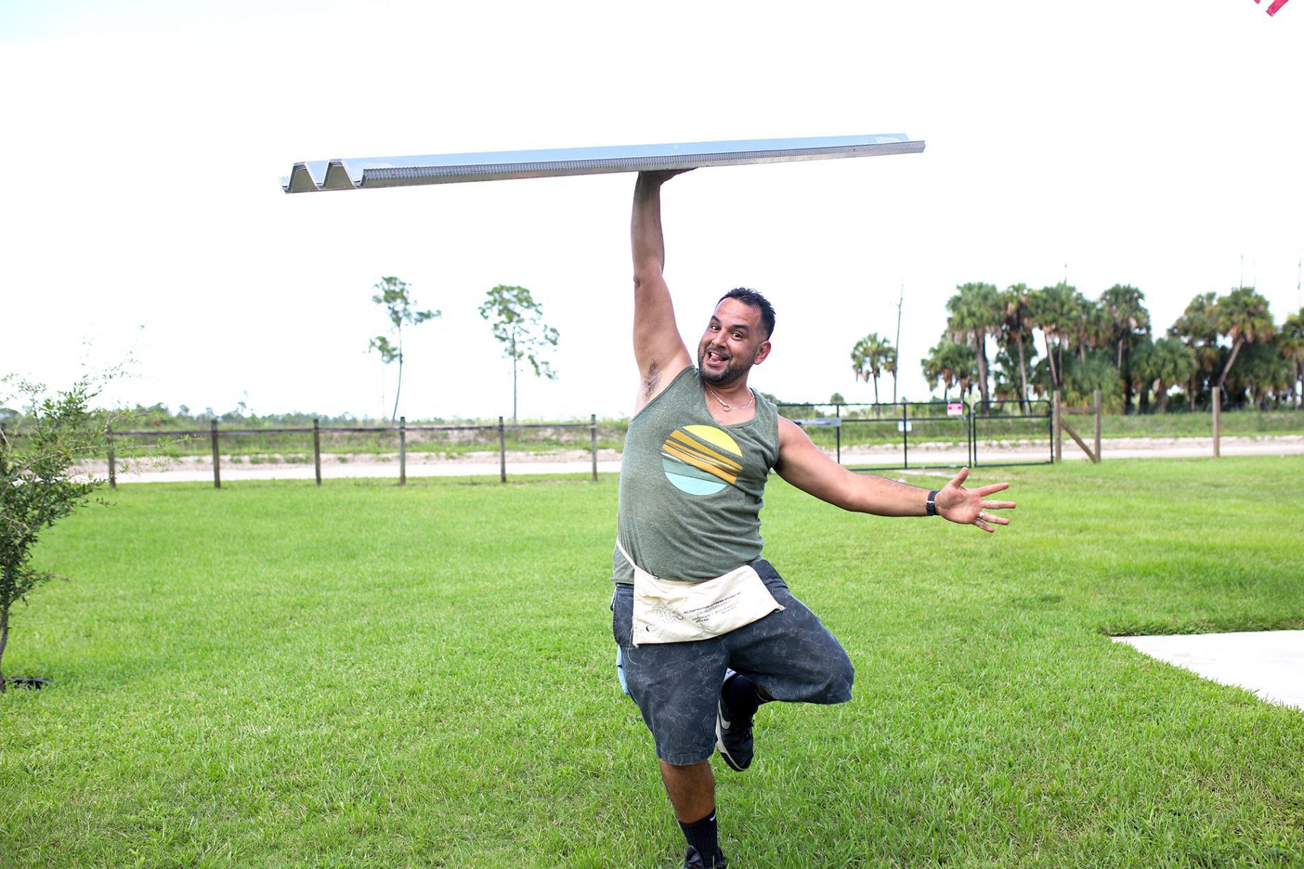 super dad balancing a hurricane shutter on his hand