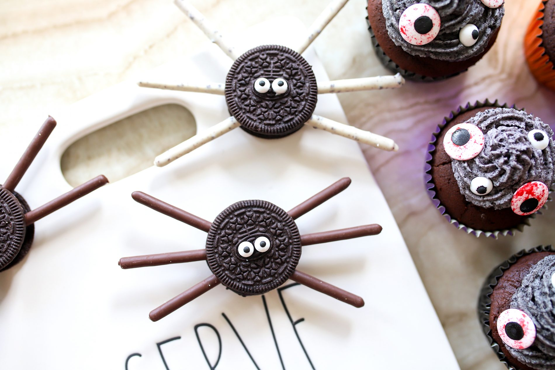 a spider made with oreo cookies and pocky on top of a are dunn serve tray