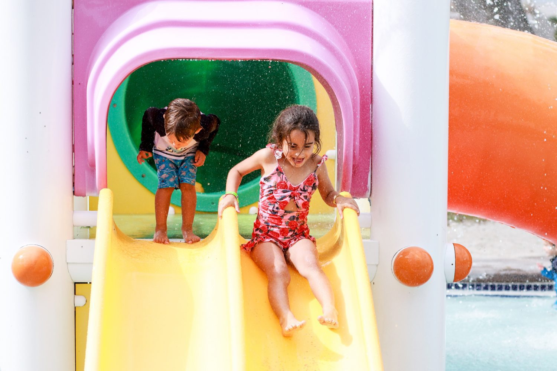 little girl sliding down a slide at a water park