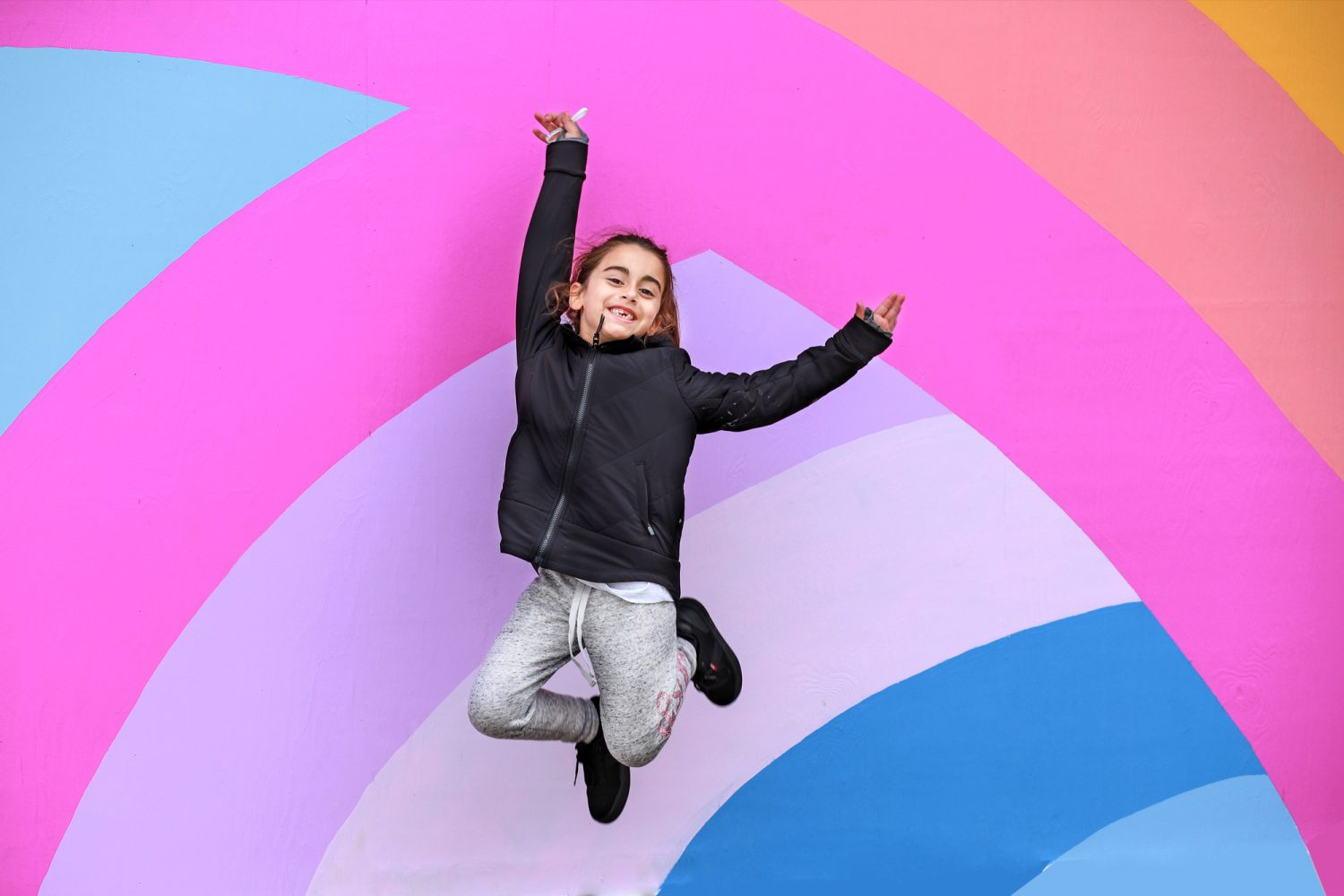 little girl jumping in front of a rainbow wall