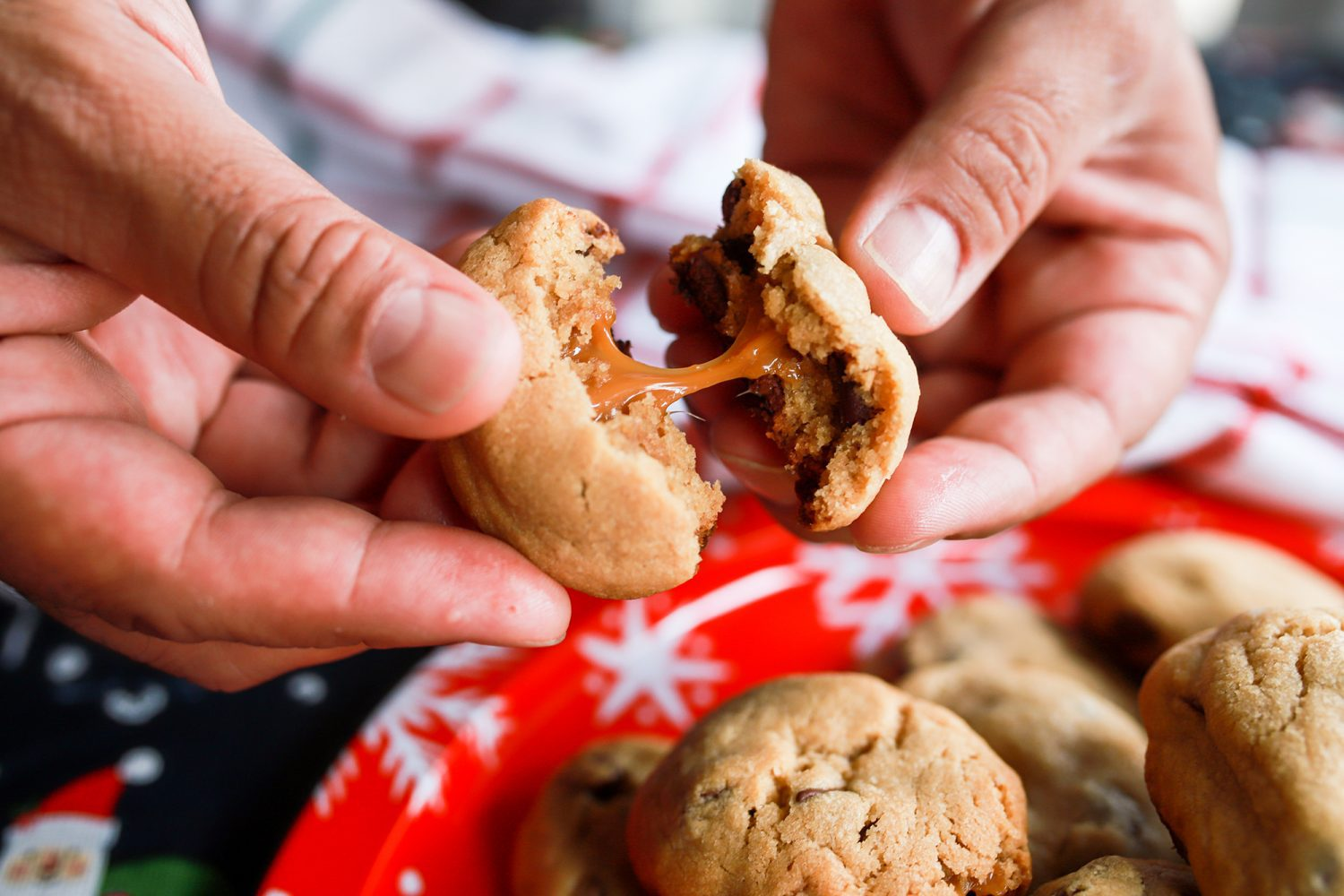 hands pulling apart a cookie filled with caramel