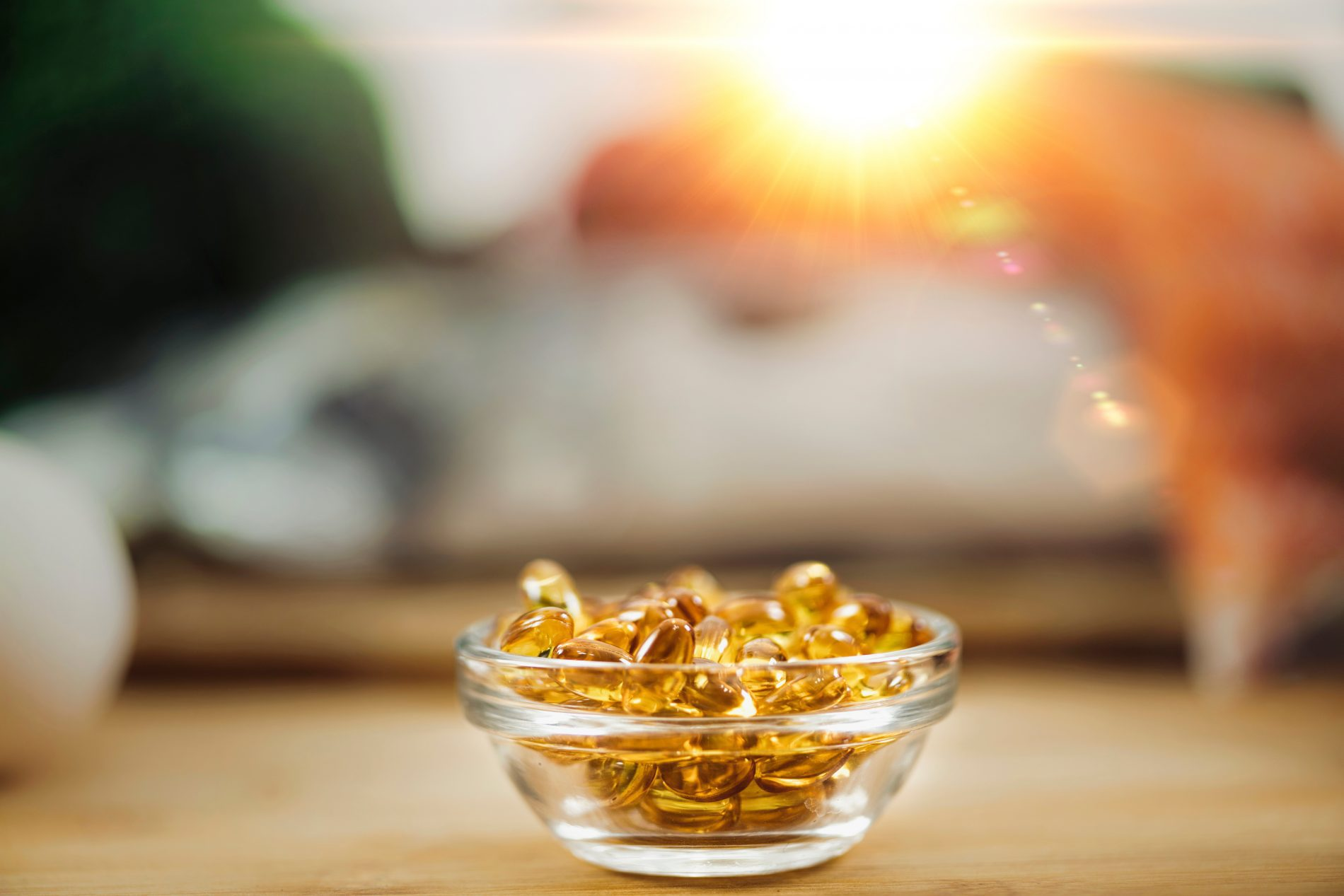 Vitamin D Supplements. Gel Capsules in Focus, Natural Sources of Vitamin D In Background