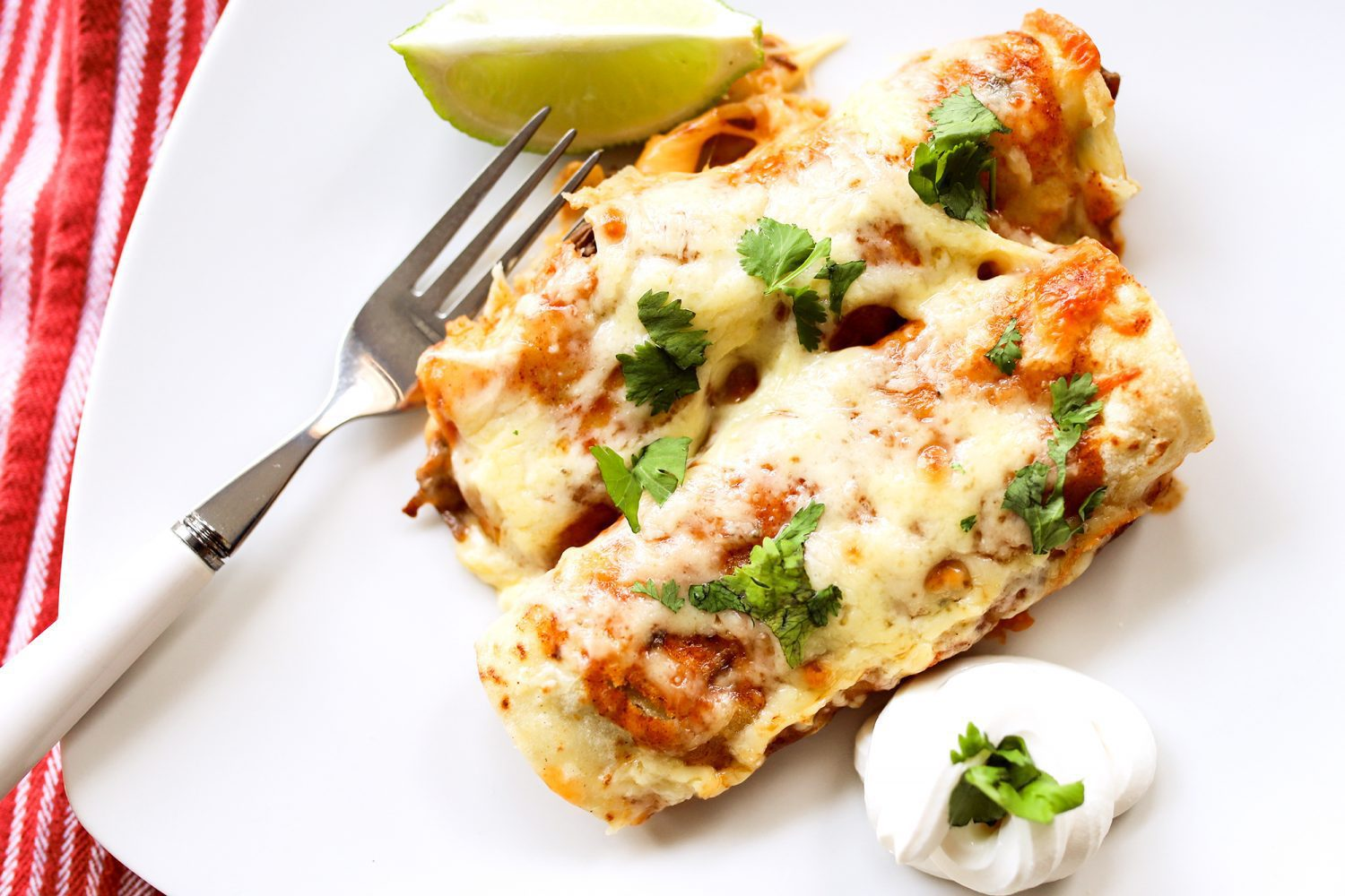 enchiladas on a plate with a fork