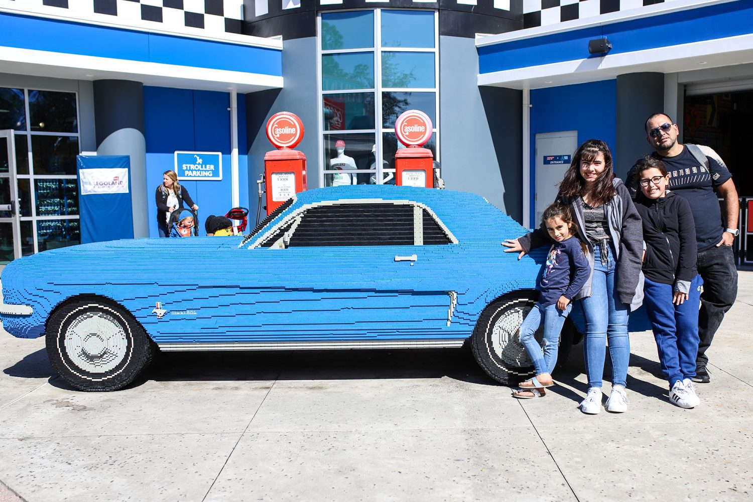 family standing in front of car made out of legos