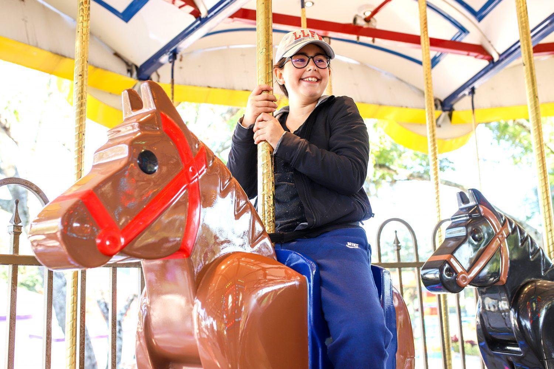 girl sitting on a carousel