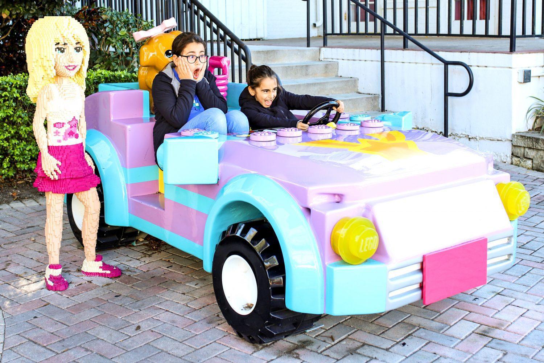girls pretending to drive a lego friends car