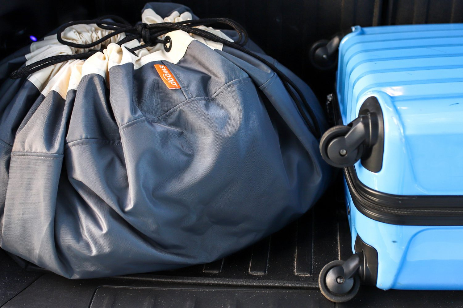 swoop bag and a suitcase in the back of a car
