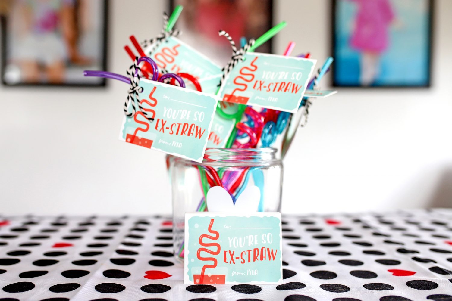 glass container filled with straws and valentine's day notes