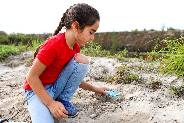 little girl using a shovel in the dirt