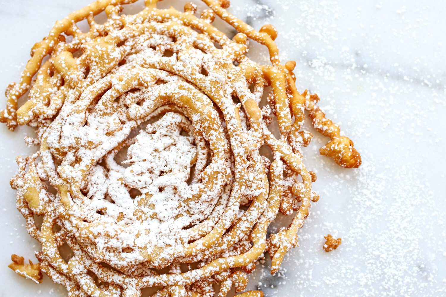 close up of a homemade funnel cake with powdered sugar