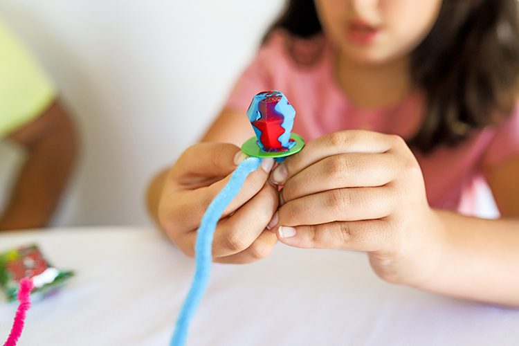 attaching a pipe cleaner to a ring pop