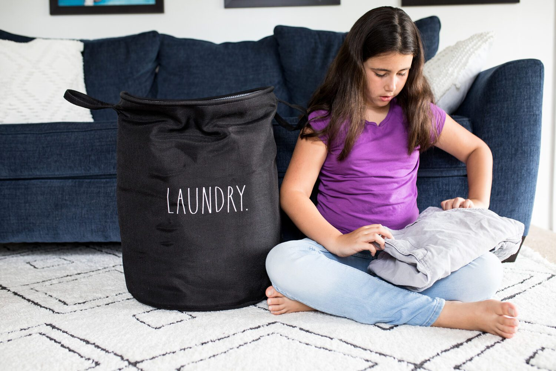 girl folding laundry next to a Rae Dunn laundry basket