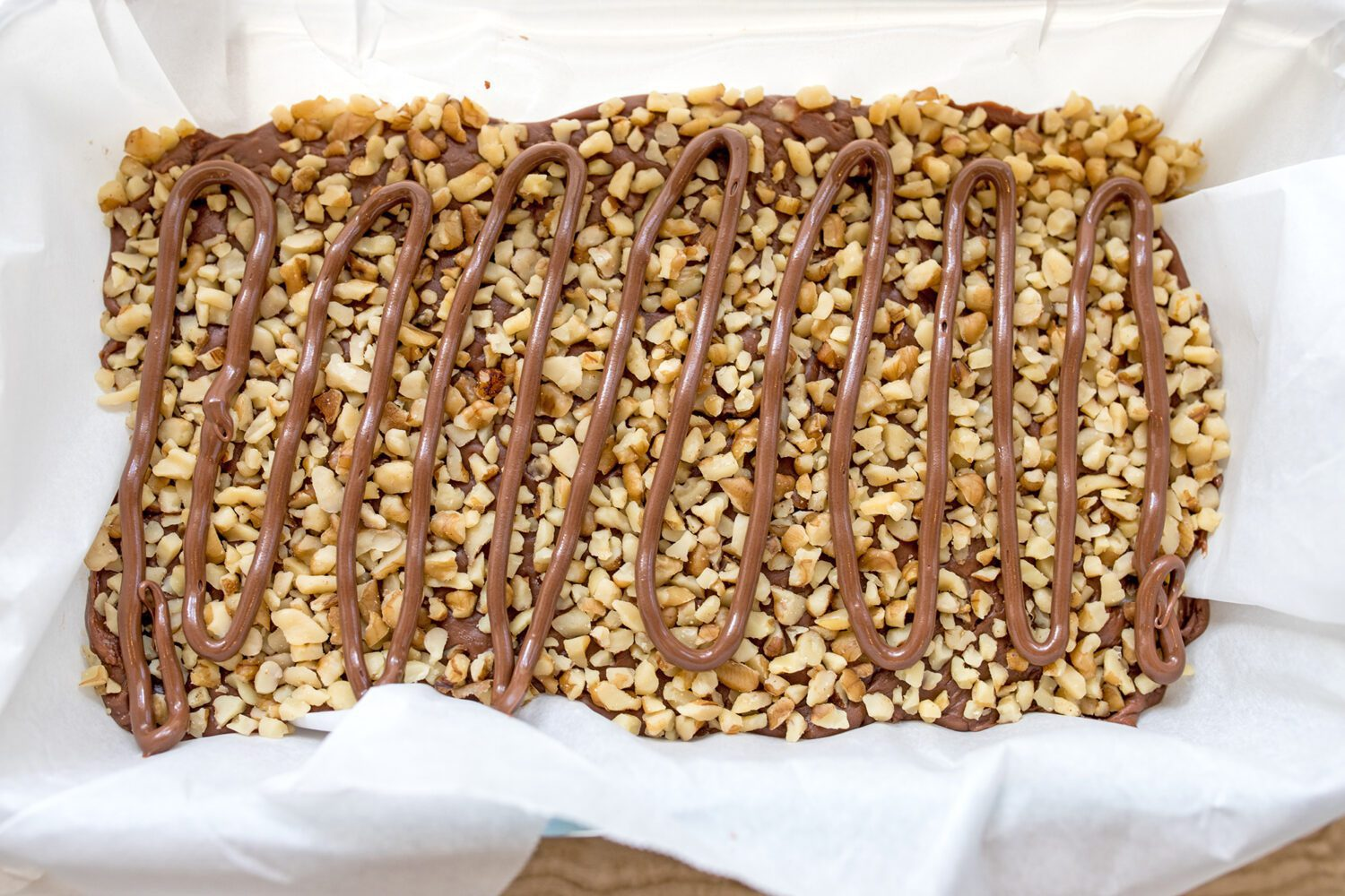 fudge topped with finely chopped walnuts and Nutella in a loaf pan