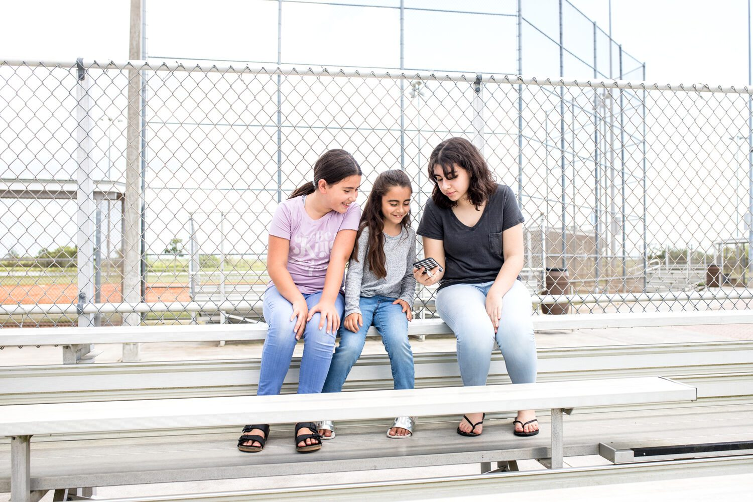three sisters sitting on the bleachers, looking at a phone