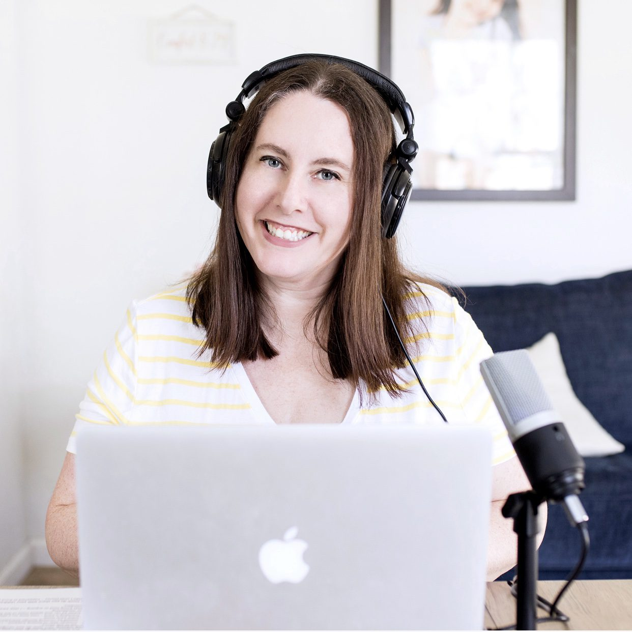 woman on podcast wearing headphones, sitting next to a laptop and external microphone