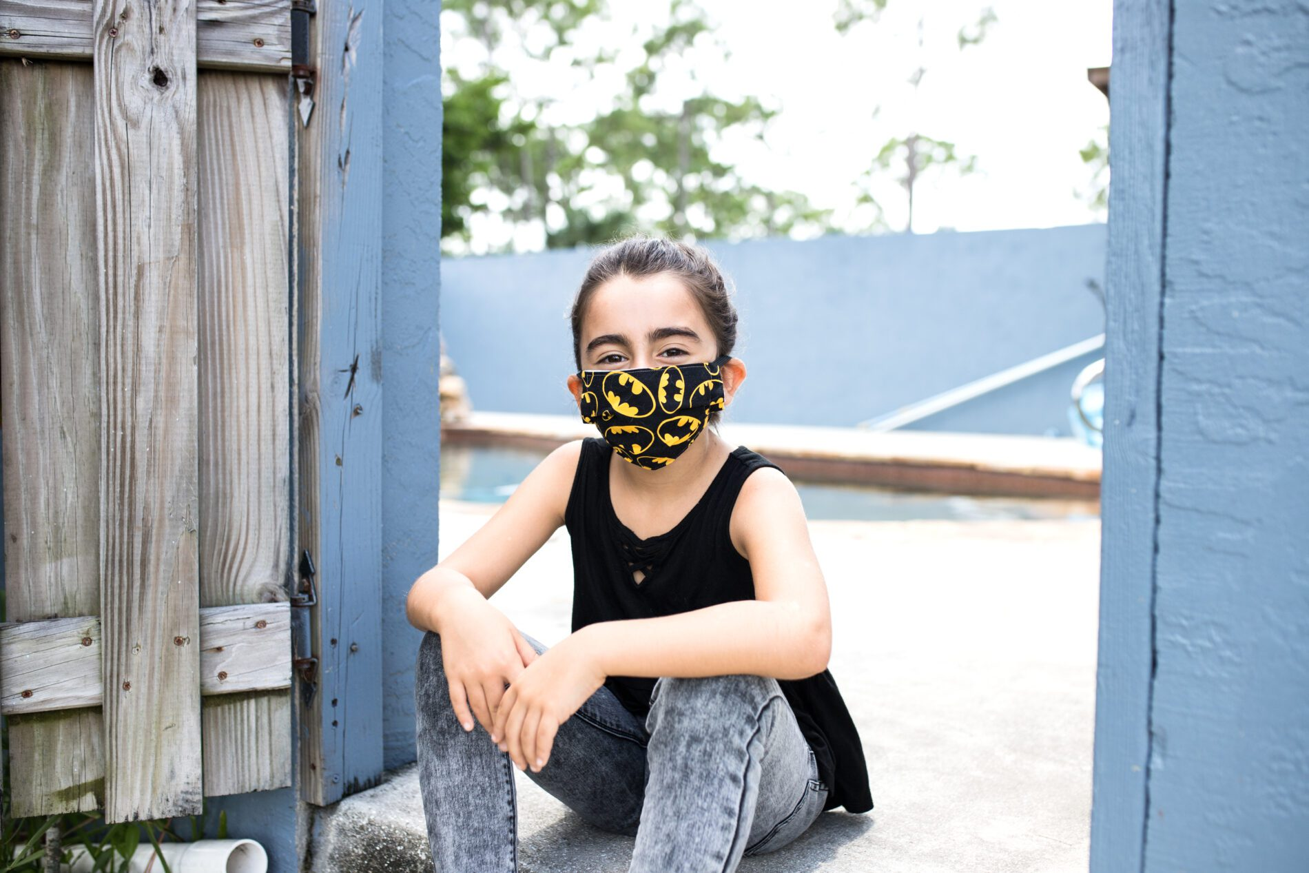 girl sitting down with a batman mask on