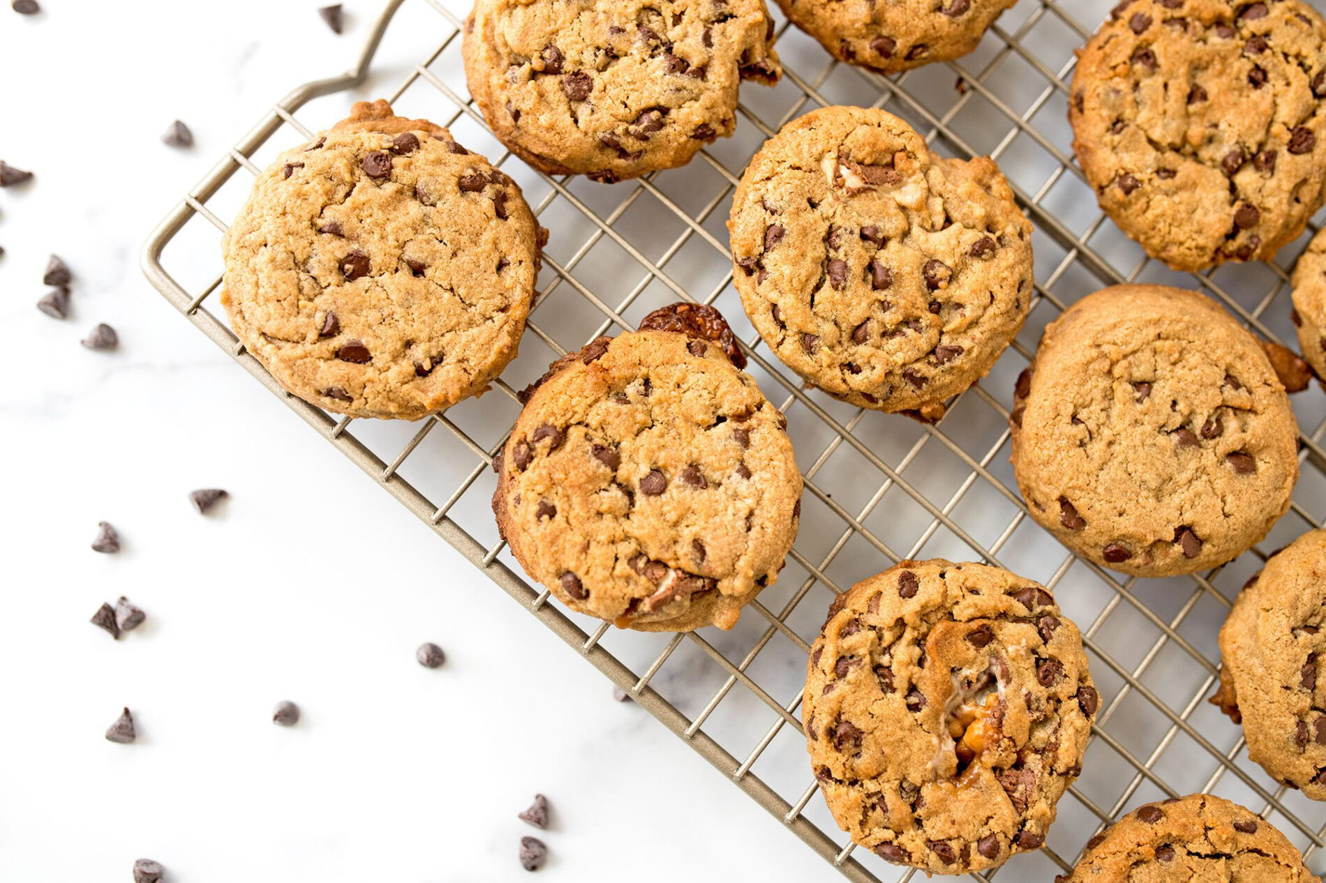 peanut butter chocolate chip snickers cookies on a cooling rack