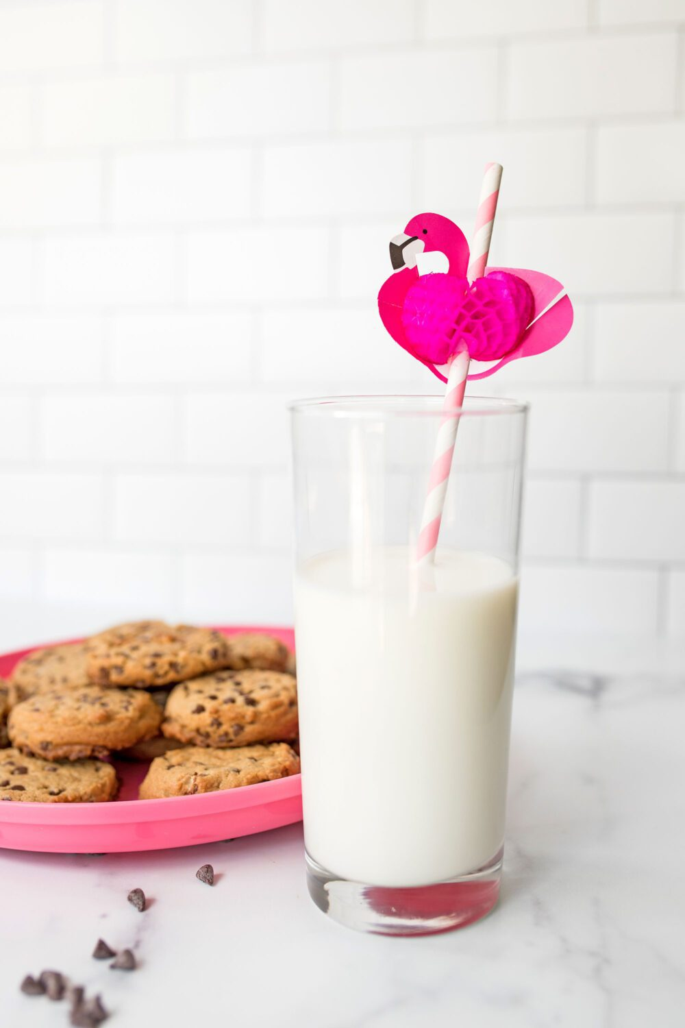 a glass of milk with a flamingo straw and cookies in the background
