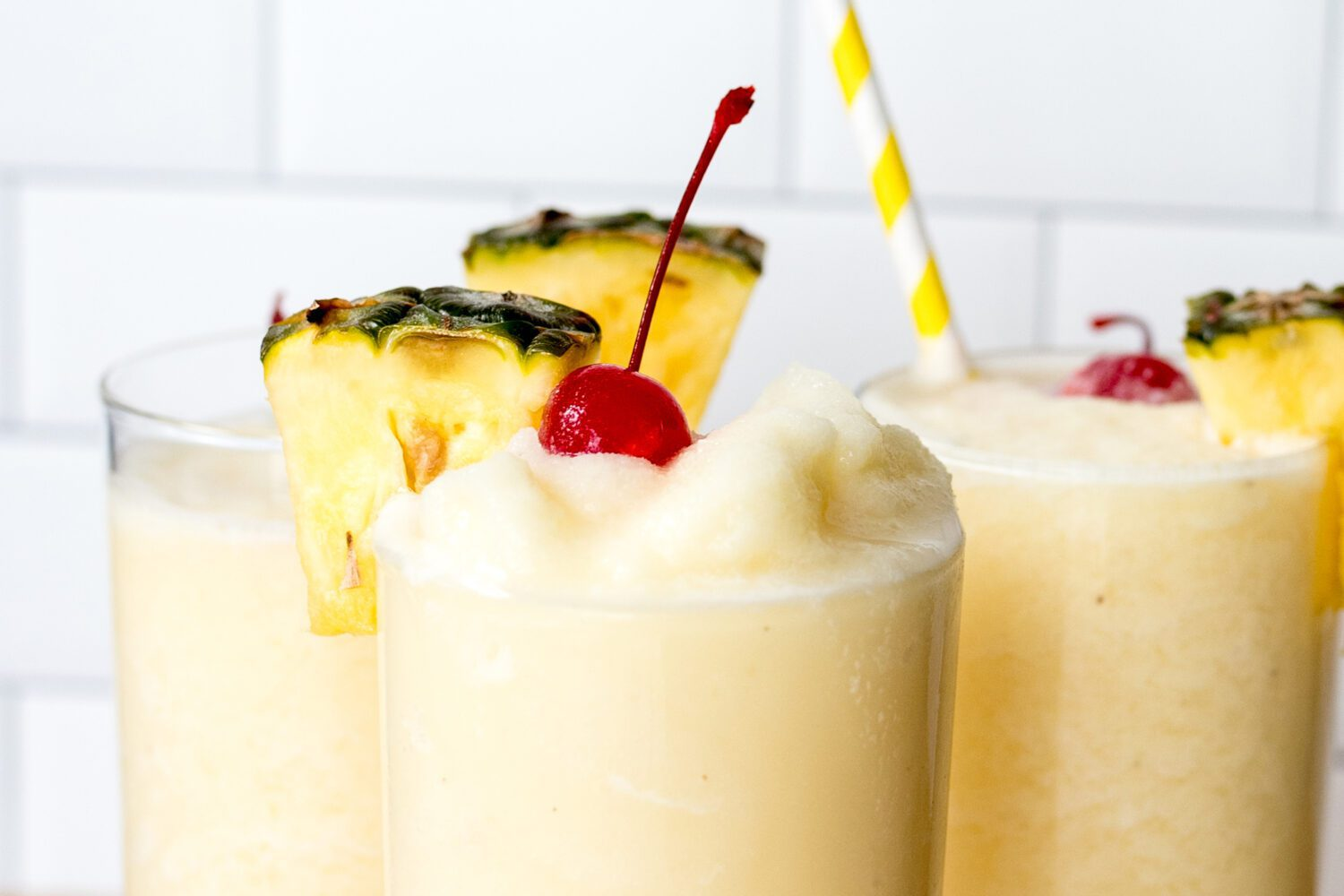 piña coladas with cherries and pineapple wedges