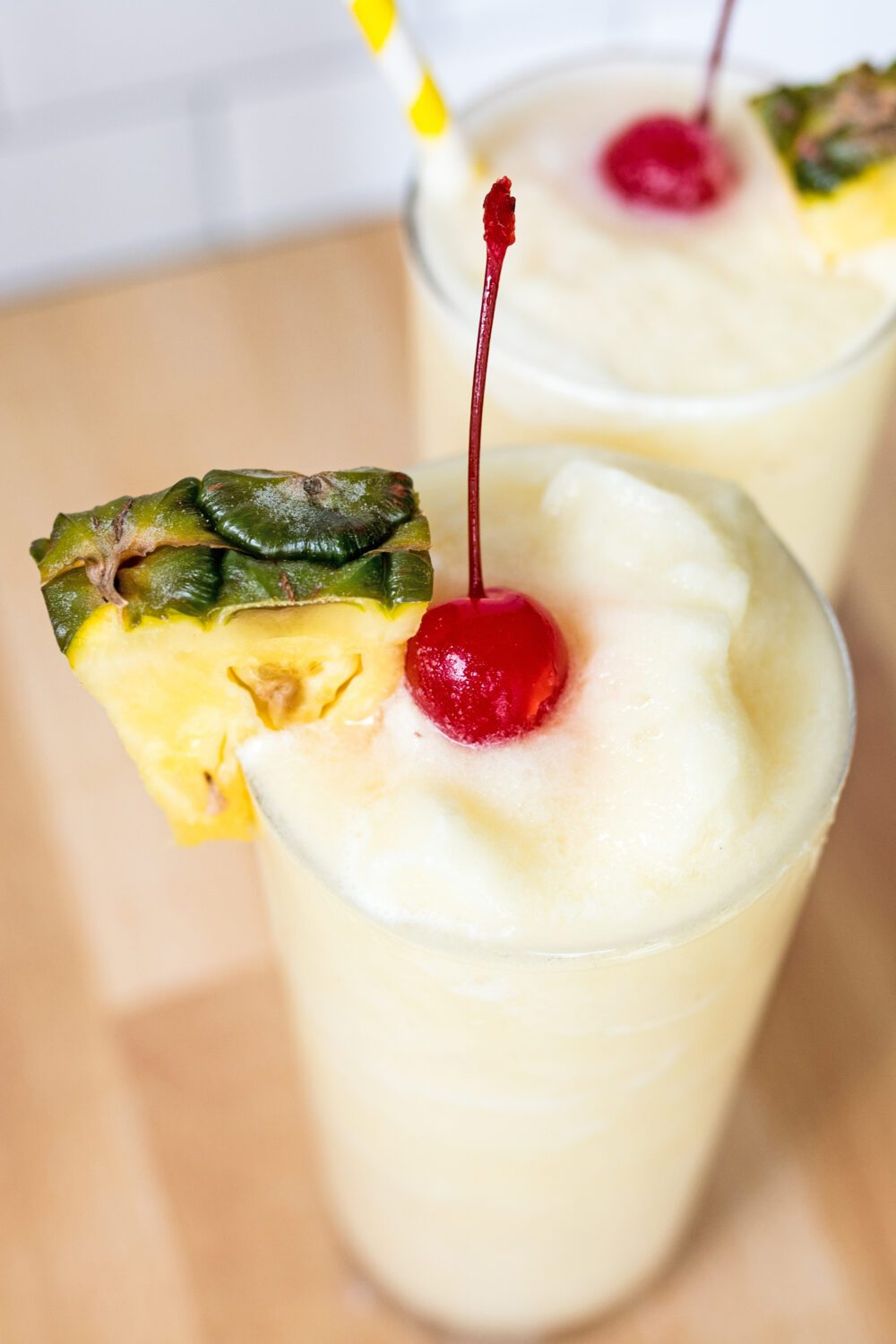 close up of a non-alcoholic piña colada with cherry and pineapple garnishes