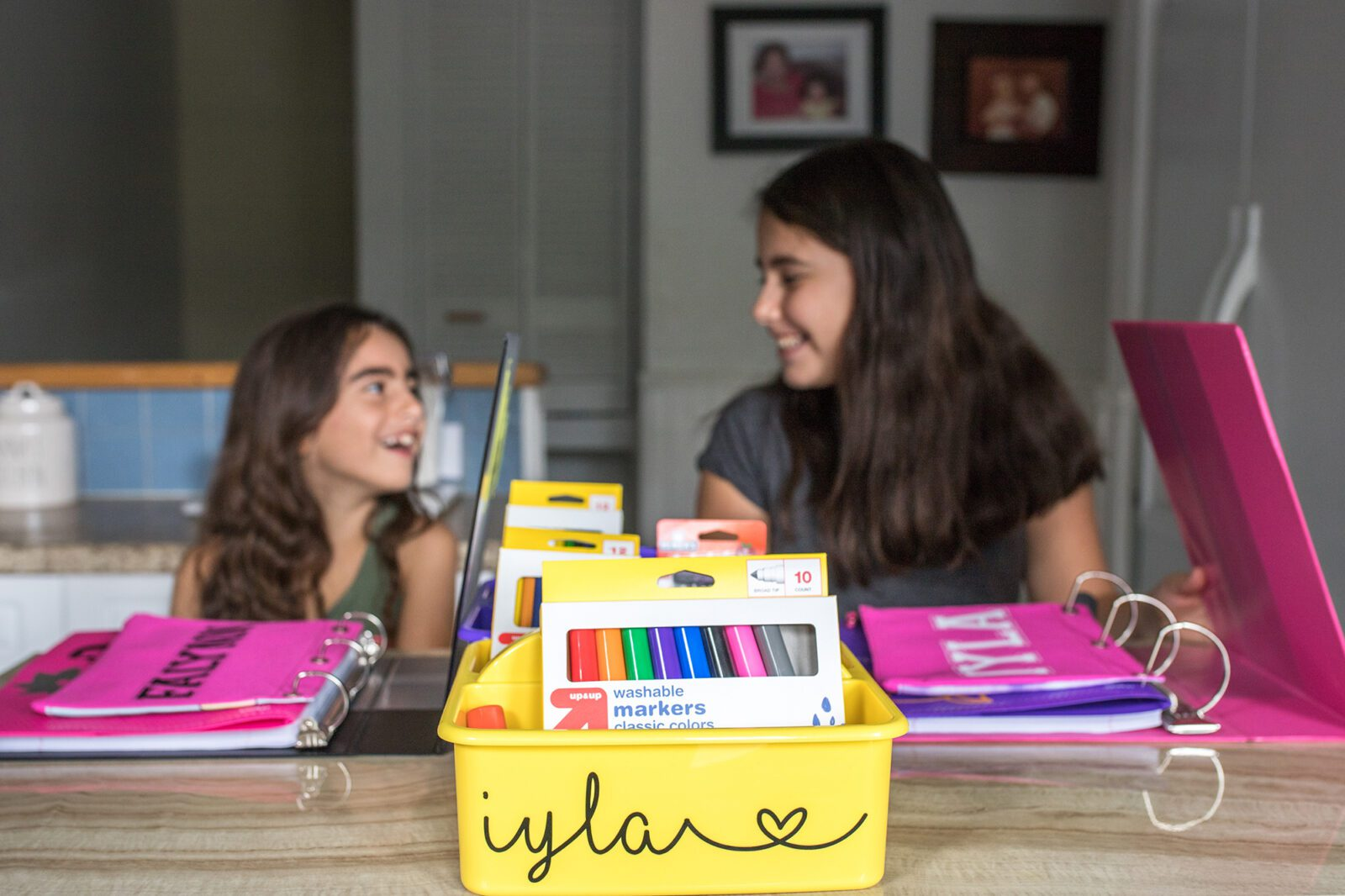 personalized storage bin with sisters smiling at each other in the background