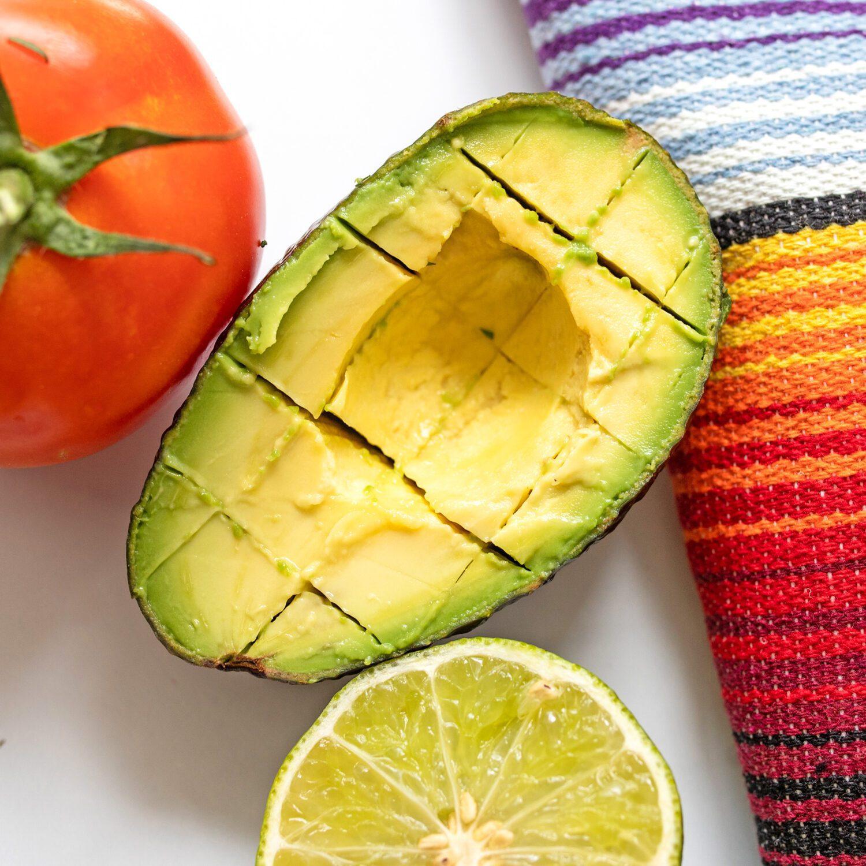 sliced avocado next to lime and tomato