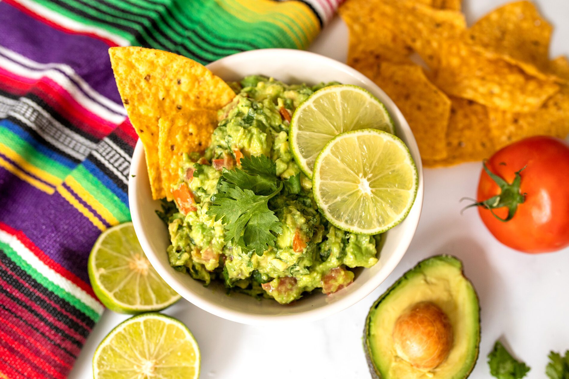 bowl of homemade guacamole with ingredients