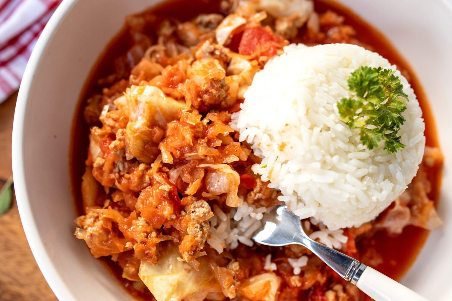 fork full of food next to a scoop of rice