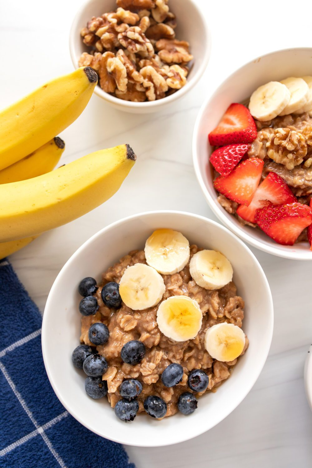 bowls full of oatmeal with fruit and bananas