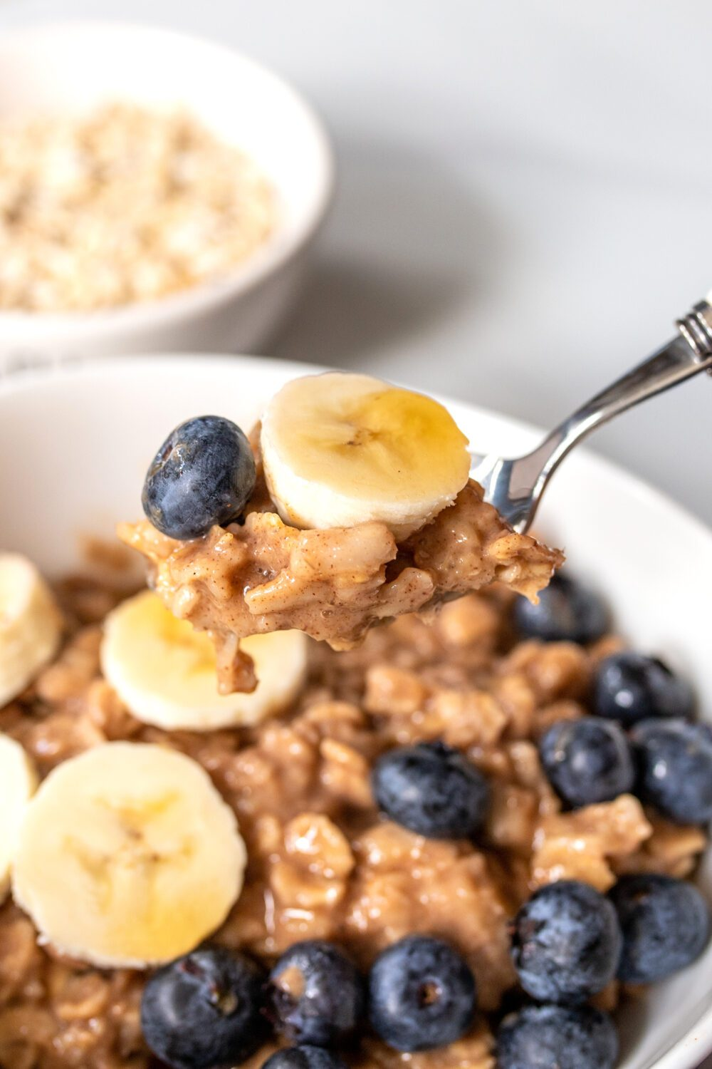 spoonful of homemade oatmeal with bananas and blueberries