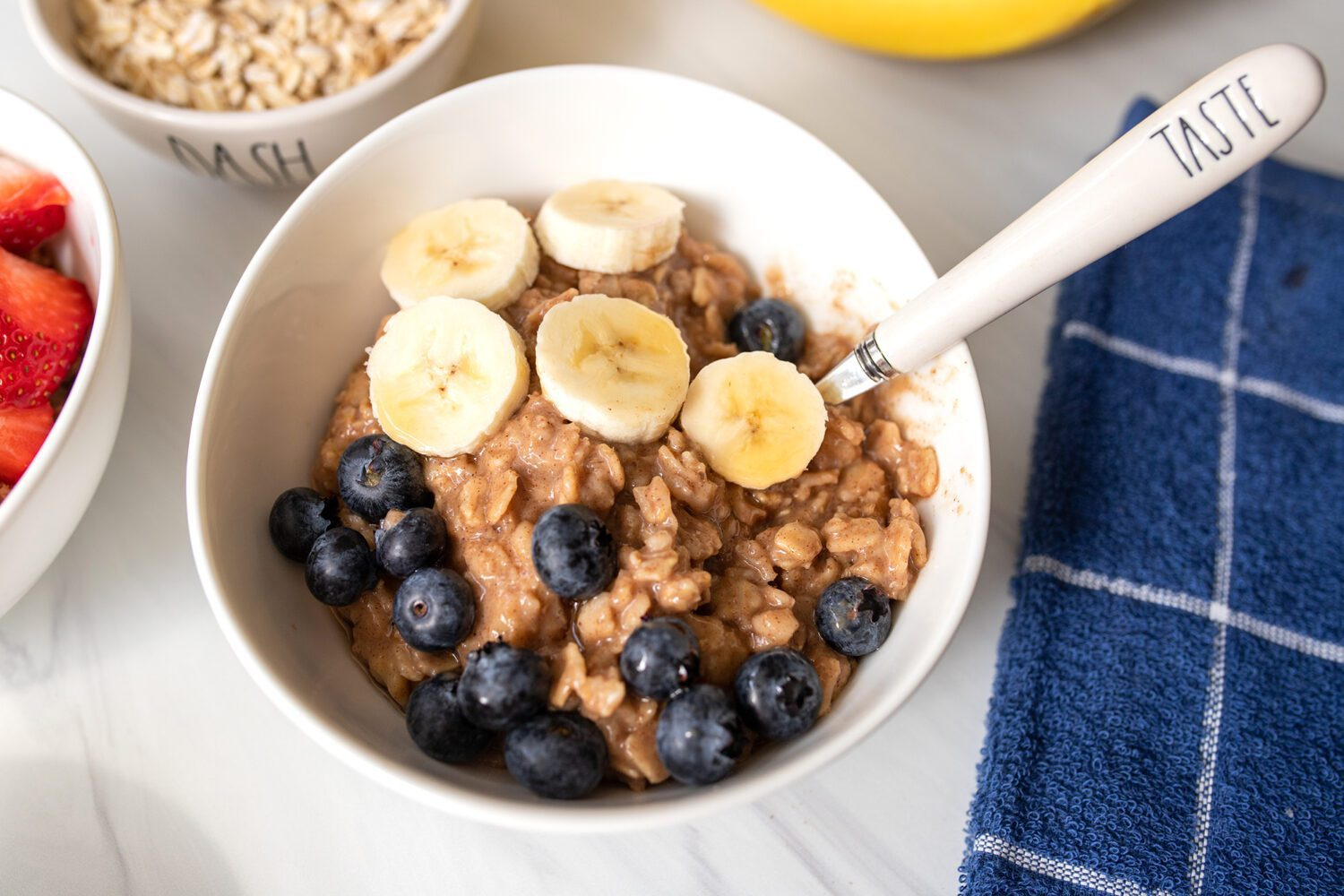 bowl of oatmeal with fruit and a rae dunn spoon