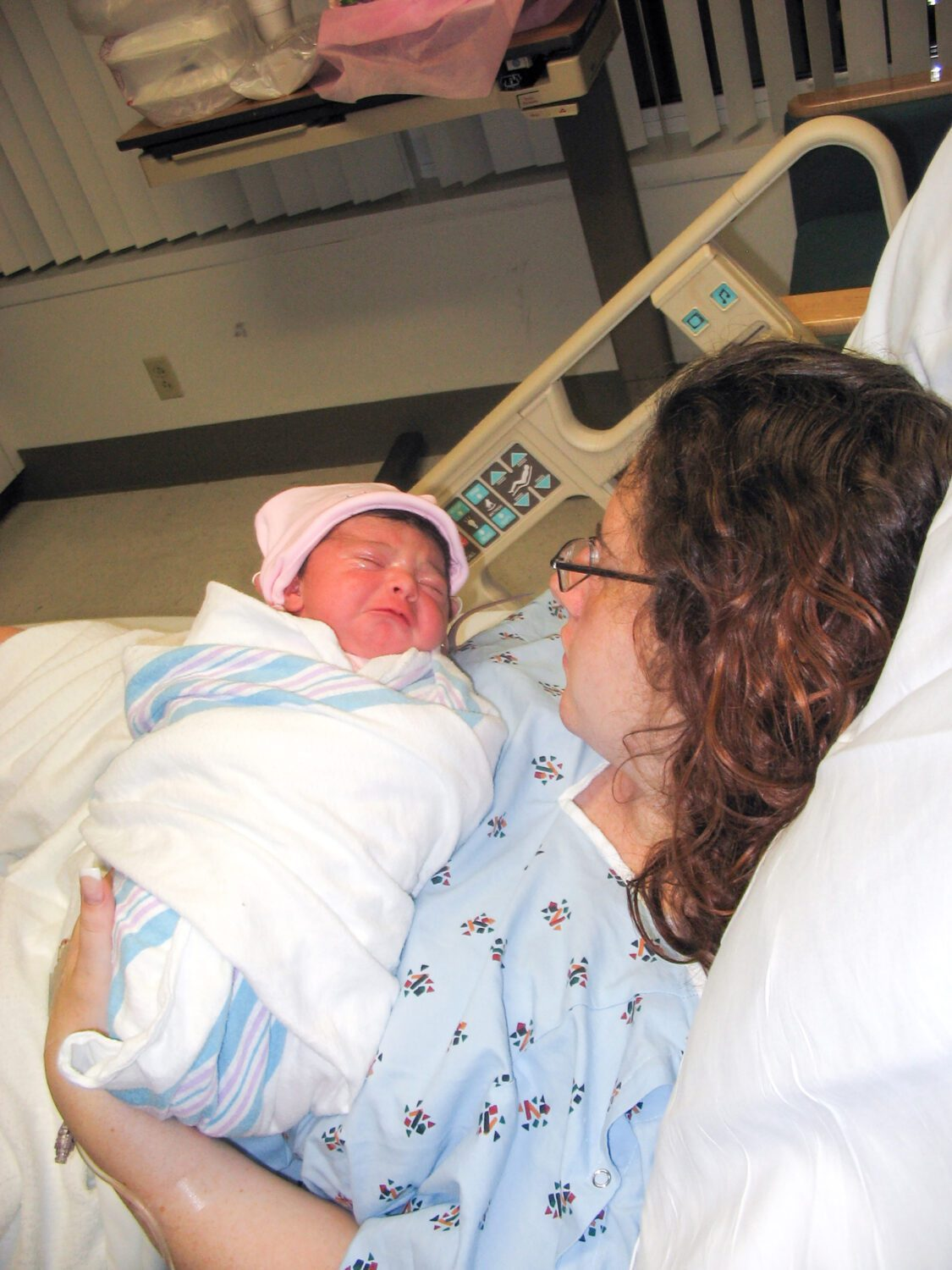 mom holding a newborn girl in the hospital