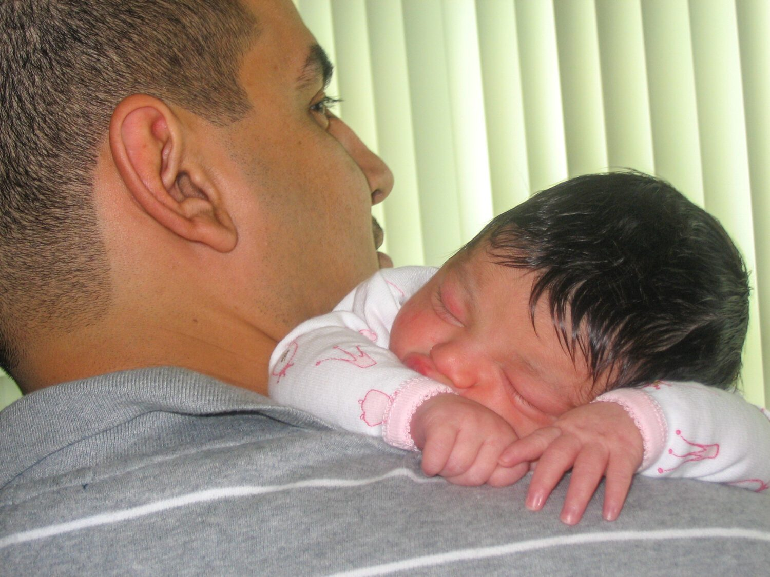newborn baby girl resting on Dad's shoulder after her birth story
