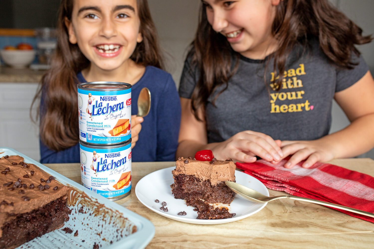sisters sitting at the counter with cake and la lechera sweetened condensed milk