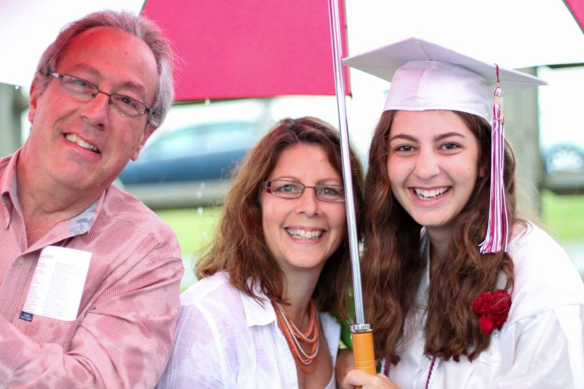 teenager with her parents at high school graduation