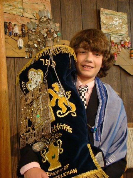 young man at his bar mitzvah holding the torah