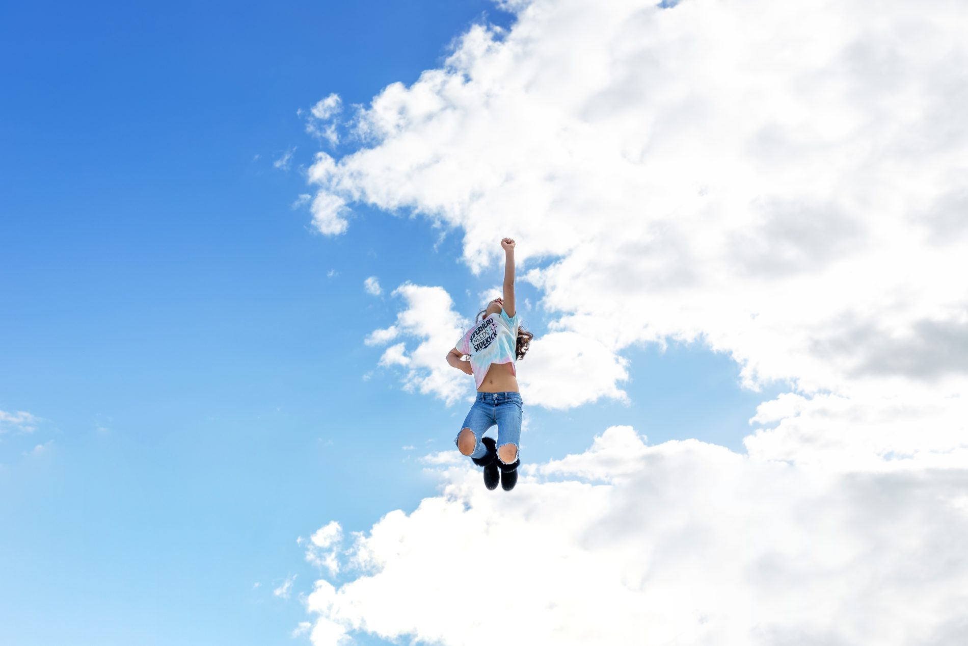girl in a super hero pose, flying through the sky