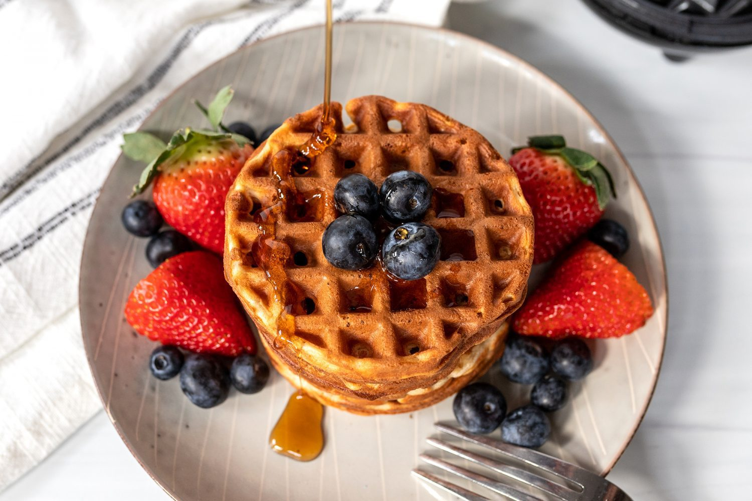 plate of greek yogurt waffles with berries and syrup