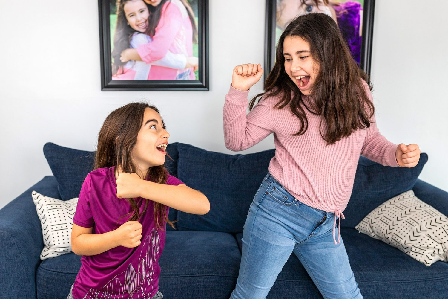 two girls dancing in front of a couch