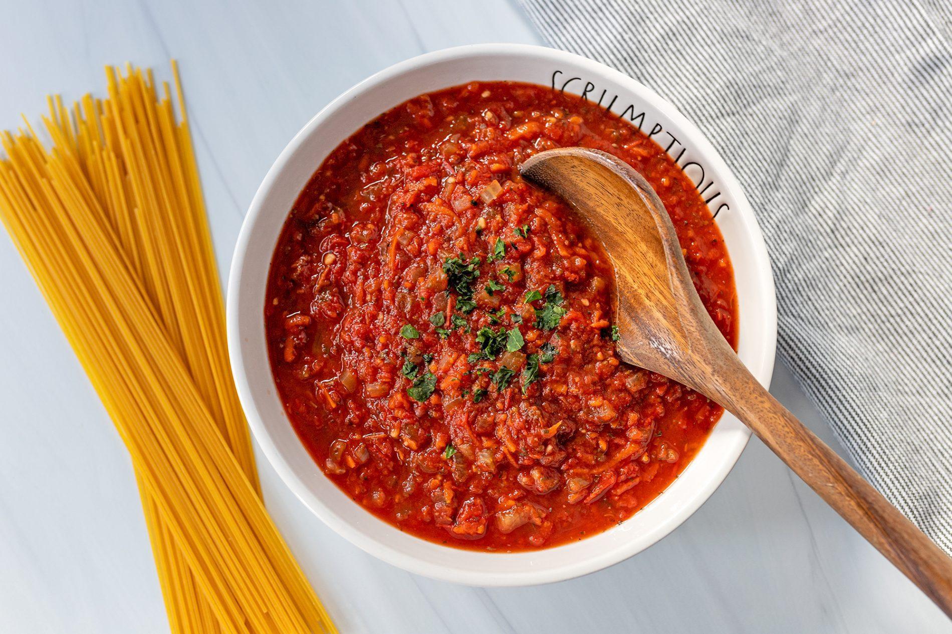 slow cooker pasta sauce next to spaghetti