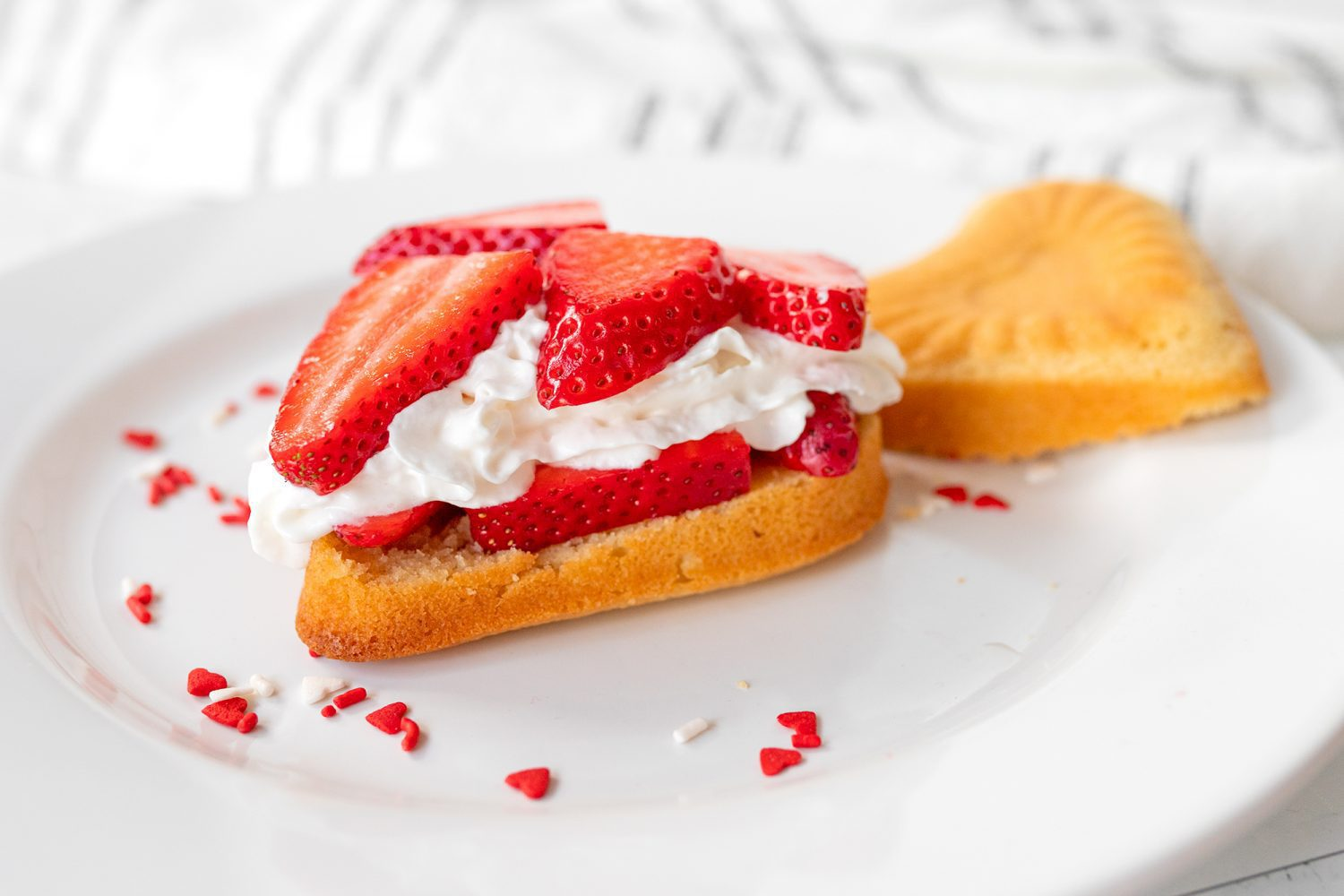 pound cake topped with fresh strawberries and whipped cream