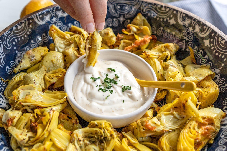 dipping an artichoke heart into garlic aioli
