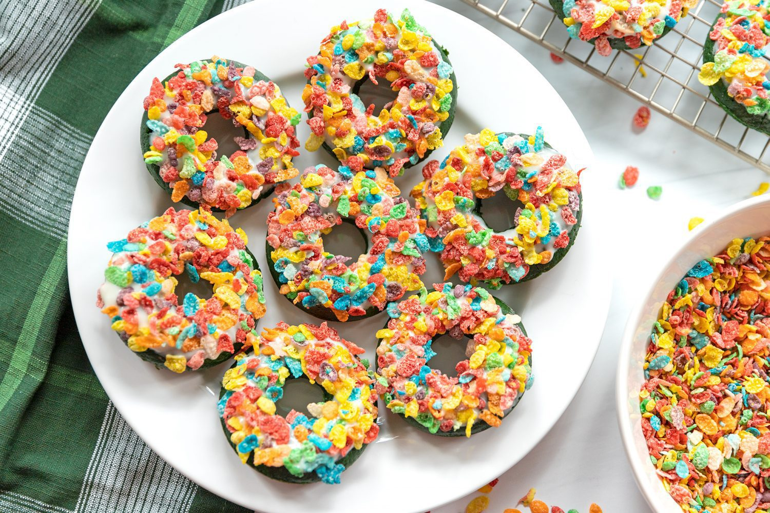round plate full of donuts covered in fruity pebbles