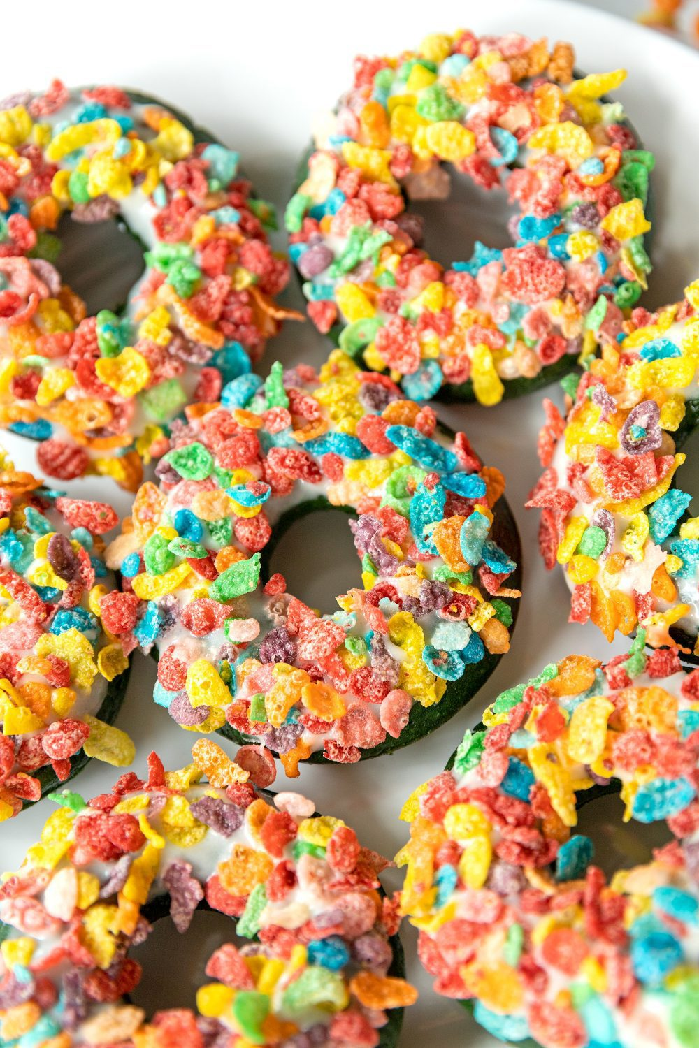 plate full of colorful baked donuts