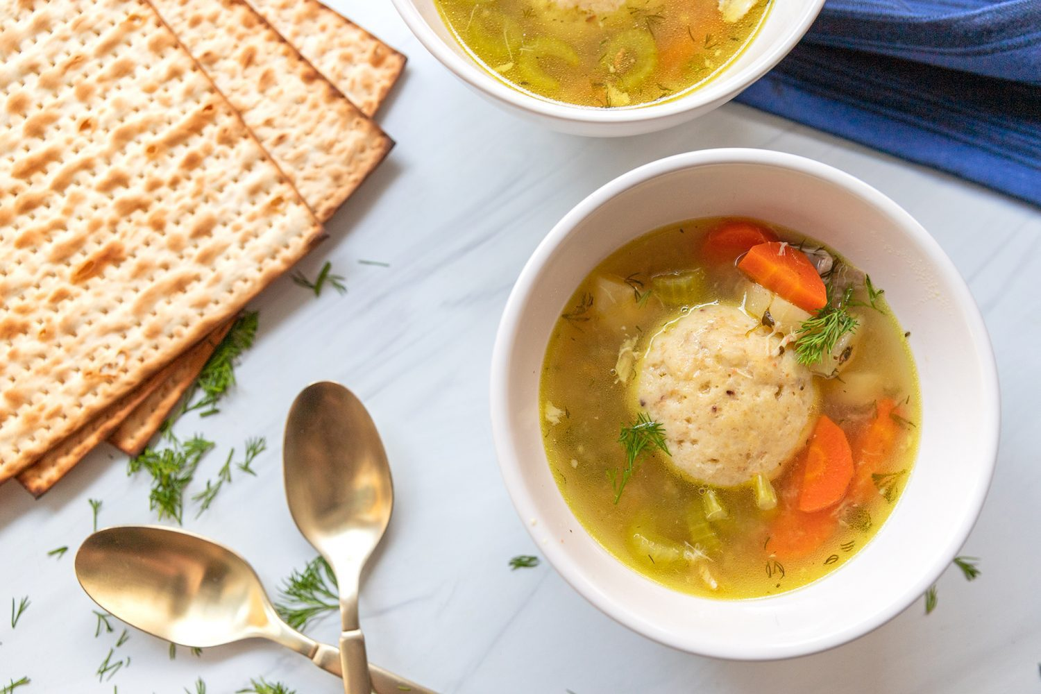 bowl of matzo ball soup with matzah and spoons